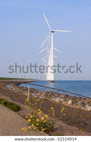 Colonade of windmills, with a blooming wallflower in front - stock photo