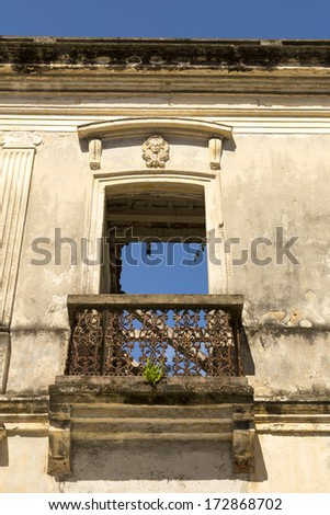 colonial balcony door in the ruins with blue sky showing through - stock photo