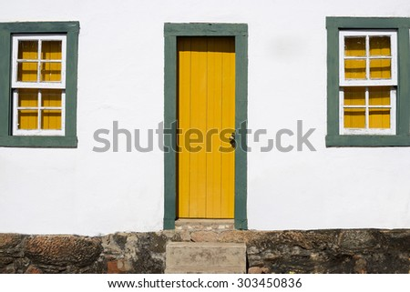 Colonial House With Yellow and Green Door and Windows - Historic Town of Tiradentes (UNESCO World Heritage) - Minas Gerais, Brazil - stock photo