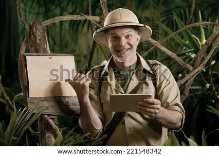 Colonial style adventurer with digital tablet exploring jungle wilderness. - stock photo