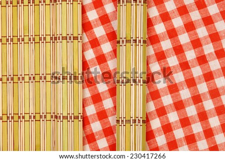 Color bamboo mat and tablecloth red and white checkered wavy on wooden table - stock photo