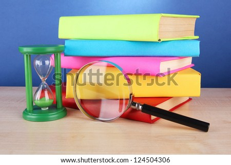 color books with magnifying glass on table on blue background - stock photo