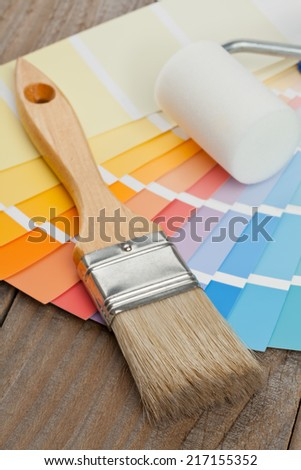 Color chart guide for renovation with brush and paint roller on wooden surface - stock photo