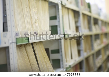 Color coded filing system on library shelves - stock photo