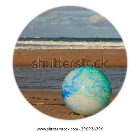 color concept image for global environmental issue using inflatable rubber ball with earth like markings against ocean beach background shaped format
