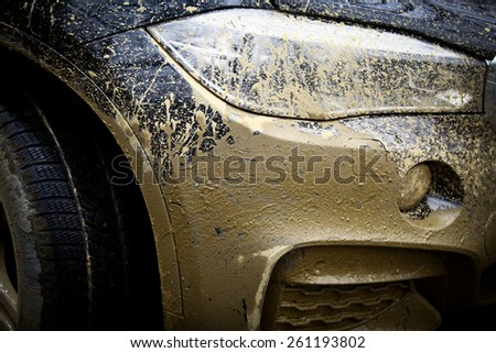 Color detail with the front side of an off-road car, covered in mud. - stock photo