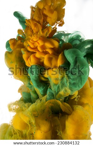 Color drop in water, photographed in motion. Ink swirling in water. Cloud of silky ink in water isolated on white background. Colorful ink underwater, ink drop. Green, orange, yellow color.