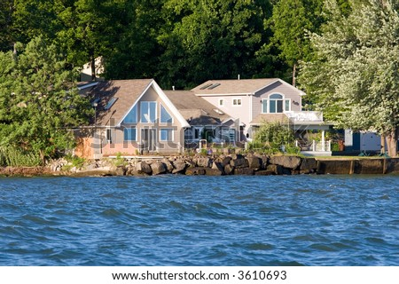Color DSLR image of a close view of a cottage vacation lake house on Ontario Lake, with water in the foreground and trees in the background. Horizontal orientation with copy space for text. - stock photo