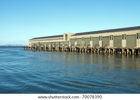 Color DSLR image of a dock and warehouse on a commercial pier, on the water of San Francisco bay. Horizontal with copy space for text - stock photo