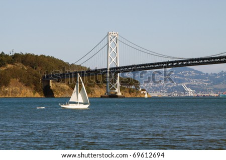 Color DSLR image of a white sailboat on the blue water of San Francisco Bay, in front of the Bay Bridge, California. Horizontal with copy space for text - stock photo