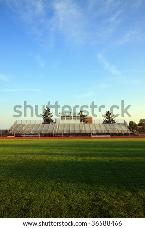 Color DSLR image of Americanl sports football stands or bleachers, as seen from green grass field at dusk with shadows and sunlight; clear, blue sky background. Vertical with copy space for text. - stock photo