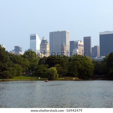 Color DSLR image of Central Park Lake, New York City; in horizontal orientation with the pond water in foreground and urban skyscrapers and skyline in background. Horizontal with copy space for text. - stock photo