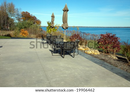 Color DSLR image of concrete patio with tables and chairs, overlooking Seneca Lake, one of the New York Finger Lakes. Horizontal with copy space for text. - stock photo