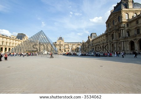Color DSLR image of courtyard and Pyramid of Louvre Museum, Paris, France. Landmark popular tourist destination houses some of the worlds greatest art treasures. Horizontal with copy space for text. - stock photo