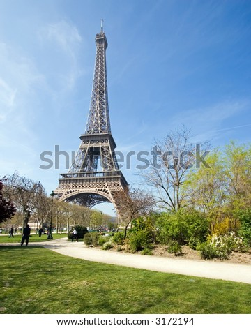 Color DSLR image of landmark tourist attraction Eiffel Tower, Paris, France, in Springtime with a green grass lawn foreground clear blue sky background. Vertical with copy space for text.