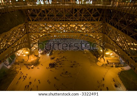 Color DSLR image of the plaza beneath the Eiffel Tower at night, Paris France. Tower is a landmark, monument and popular tourist destination, as see by people in the pools of light. Horizontal. - stock photo