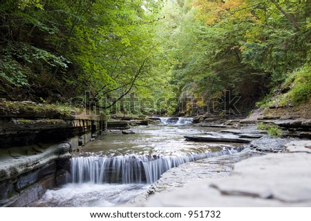 Color DSLR landscape picture of a small stream and waterfall, with green trees and a stone wall, Stony Brook, New York.  The image is in horizontal orientation with copy space for text. - stock photo