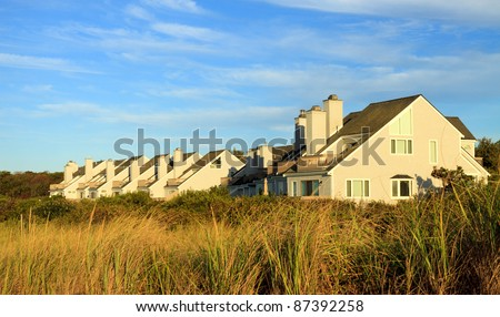 Color DSLR landscape picture of luxury Cape Cod, Massachusetts luxury vacation beach houses.  Homes are lit by golden sunset.  Horizontal orientation with copy space for text - stock photo