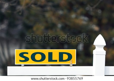Color DSLR picture of a yellow and black sold sign on real estate; in horizontal orientation with copy space for text - stock photo