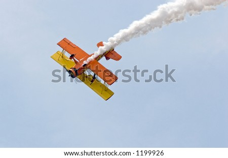 Color DSLR picture of a yellow and orange stunt plane diving through blue sky.  Speeding dangerous biplane trailing white smoke contrail.  Horizontal orientation with copy space for text. - stock photo