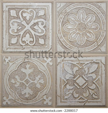 Color DSLR picture of square decorative ceramic tiles.  The the four individual tiles each have a different pattern.  The tiles are off white and useful as background, or border. - stock photo