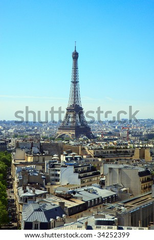 Color DSLR picture of the Eiffel Tower, Paris, France, in vertical orientation, with the skyline of Paris in the foreground and background.  Bright, clear blue sky background.  Copy space for text.