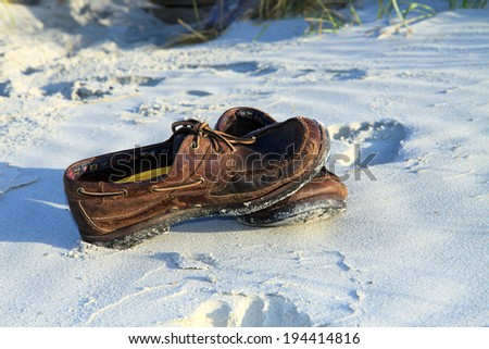 Color DSLR picture of weathered brown boat shoes on the beach sand by the shore; in horizontal orientation with copy space for text - stock photo