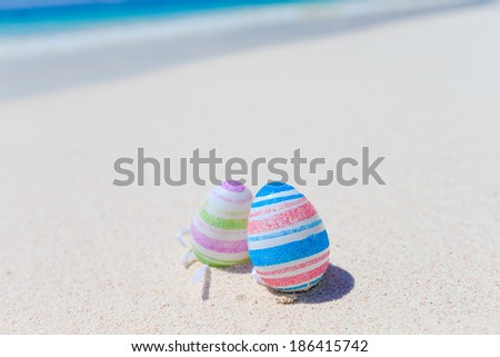 color Easter eggs on the sandy beach by the ocean  - stock photo