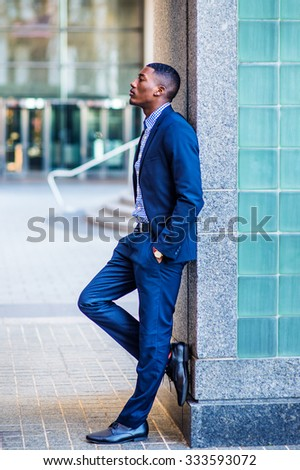 Color #1F2A44 filtered look. African American businessman working in New York. Wearing blue suit, leather shoes, a young black guy standing against wall on street, looking up, sad, deeply thinking.   - stock photo