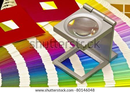 Color guide for offset print with a magnifier lens over the table - stock photo