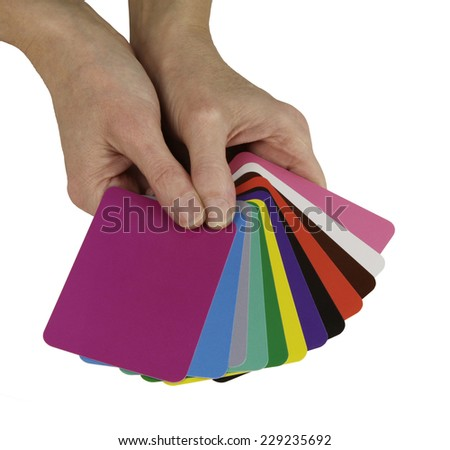 Color Healing Cards - Color therapist holding a selection of different colored cards fanned out and gesturing to take one, on a white background - stock photo
