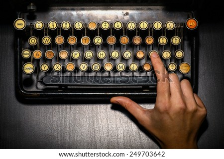 Color horizontal detail of the keyboard of an old typewriter and a hand. - stock photo