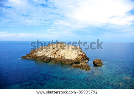 Color horizontal image of a mountain in the middle of the sea. Summer shot of and island. - stock photo