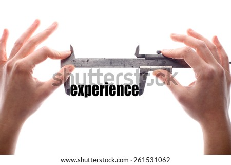 """Color horizontal shot of two hands holding a caliper measuring the word """"experience"""". - stock photo"""