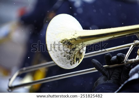 Color image of a trombone being played on a snowy day. - stock photo