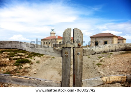Color image of a wood fence with a lighthouse behind. - stock photo