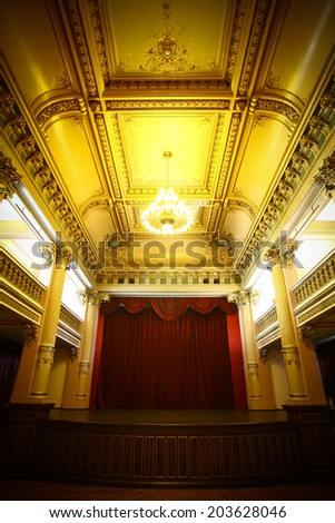 Color image of an old theater room with stage and a curtain. - stock photo