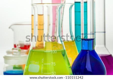 Color laboratory glassware over white background - stock photo