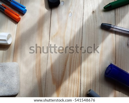 Color of pens and rubber from above on vintage wood table and sunlight. Empty ready for your message display