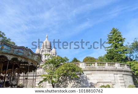 Color outdoor architectural image of the basilica Sacre Coeur, Paris, France, taken on a sunny fall day with blue sky and some clouds, trees and a roundabout / carousel