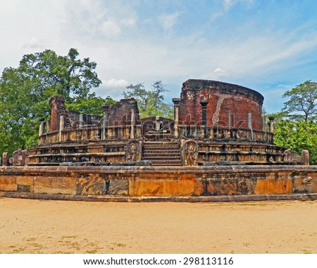 Color Painting Sacred Meditating Buddha Statue in Ruined Ancient Pagoda in Anuradhapura Archaeological Park, Sri Lanka on Sandstone Texture - stock photo