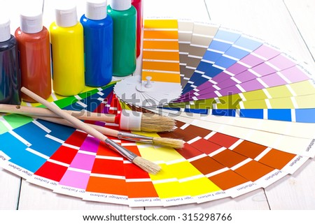 color palette, brush on white wooden background, close up - stock photo
