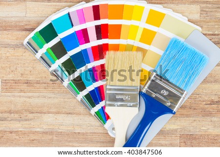 Color palette guide and brushes on wood  - stock photo