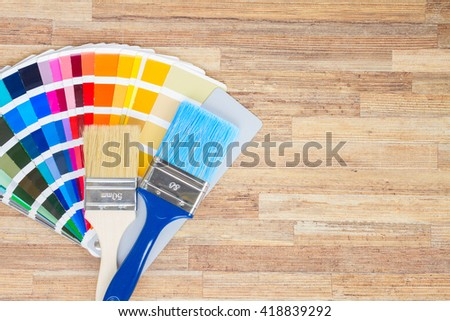 Color palette guide and brushes on wooden background with copy space - stock photo