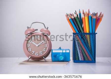 color pencil box and alarm clock on wooden table - stock photo