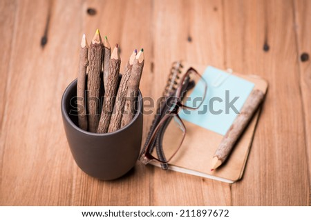 color pencil made of branches in cup with glasses and note book on wood background - stock photo