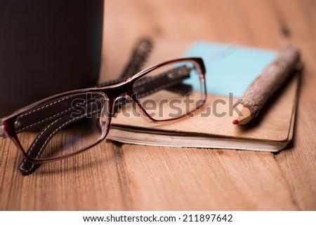 color pencil made of branches with glasses and note book on wood background - stock photo