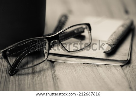 color pencil made of branches with glasses and note book on wood background,Old color style - stock photo