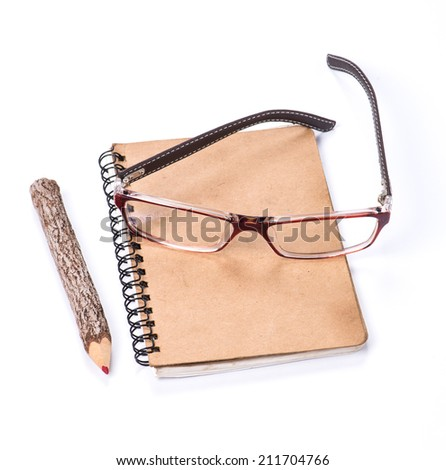 color pencil made of branches with glasses and notebook on white background - stock photo