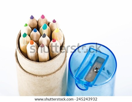 Color pencils and pencil sharpener on white background - stock photo